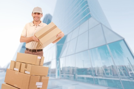 moving office: Friendly courier with lots of boxes in a financial district
