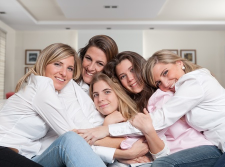 A group of five happy women of different ages hugging in the living room photo