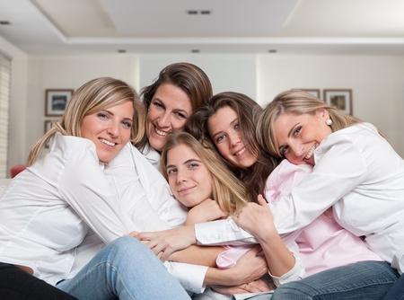 Een groep van vijf gelukkige vrouwen van verschillende leeftijden knuffelen in de woonkamer