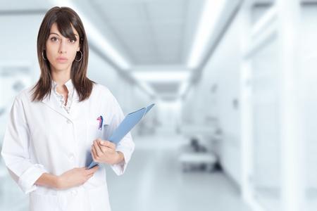 historia clinica: Una enfermera joven que sostiene una carpeta, de pie junto a un pasillo del hospital