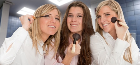 Three young women getting ready for going out, applying make-up photo