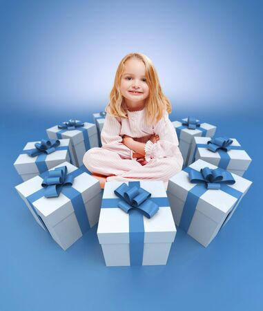 blue gift box: Smiling little girls in her pajamas surrounded by gifts