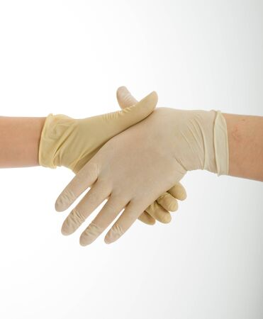 Handshake with hands wearing latex protective gloves