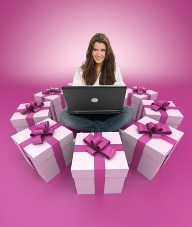 Young girl sitting with a laptop surrounded by gift boxes photo