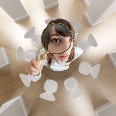 investigating: Aerial view of a young woman looking above through a magnifying glass