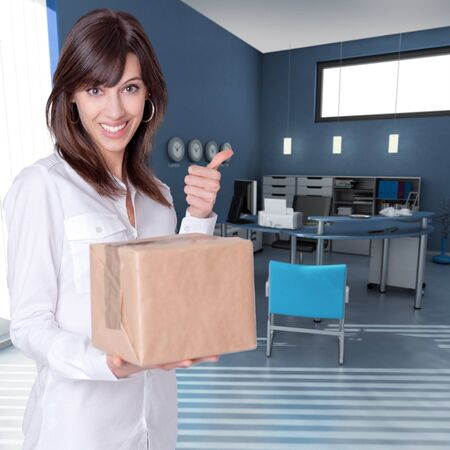 Happy young woman holding a box in an office with her thumb up Stock Photo - 13197380