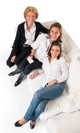 three generations of women:  Aerial view of three smiling women of different ages on a white sofa  Stock Photo