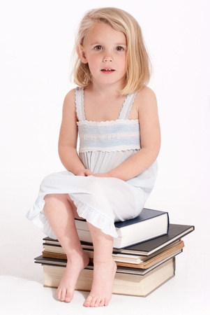 nighttimes:  Cute little blonde girl in a nightdress sitting on a pile of books