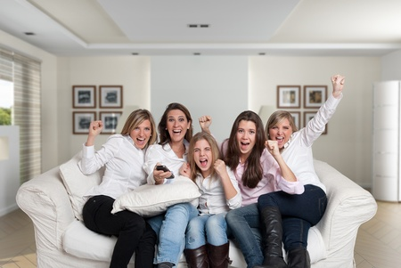 A group of  female family members sitting at home cheering photo