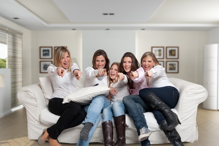 A group of five happy women of different ages laughing in the living room pointing at the camera Stock Photo - 13230478
