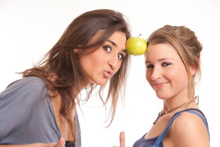 Two girls holding an apple with their foreheads photo