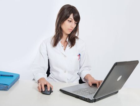 Young female healthcare worker working at her laptop with a pile of folders on the desk photo