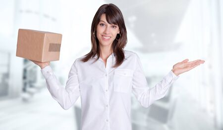 send parcel: Young woman with a balance position a parcel in one hand and the other one empty against a business background Stock Photo