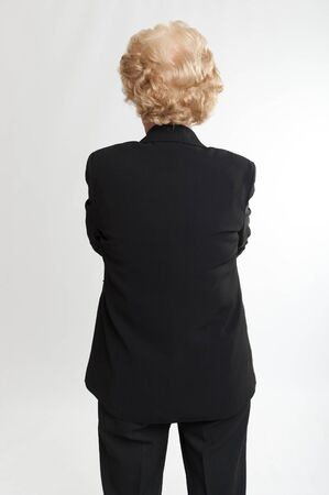 Back view of a blonde mature woman in a black suit photo