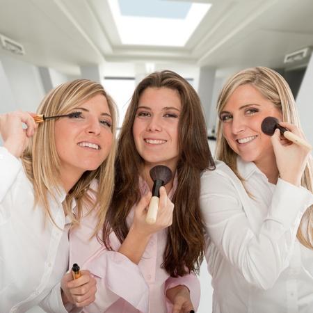 going out: Tre giovani donne stanno preparando per uscire, applicare il make-up Archivio Fotografico