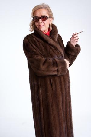 mink: Fumo Senior signora che indossa una pelliccia di visone e occhiali da sole