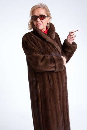 cigar smoking woman: Smoking Senior lady wearing  a mink coat and sunglasses