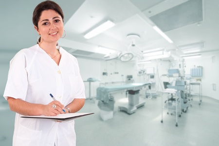 nhs: Smiling female healthcare professional taking notes with an operating room at the background