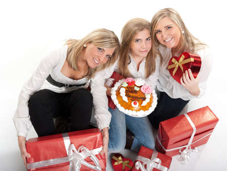 Three sisters in her teens with an anniversary cake and lots of presents photo