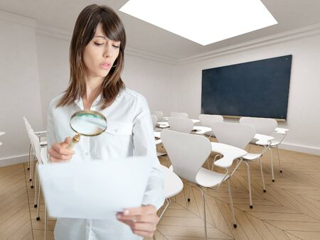 investigate: Young woman examining a paper through a magnifying glass in a seminar room
