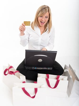 Exstatic young blond woman holding a credit card in front of a computer surrounded by shopping bags Stock Photo - 13253208