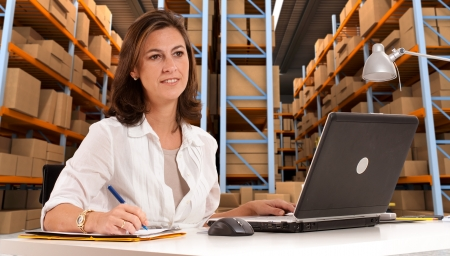 shipping supplies: Female administrative in a desk with a distribution warehouse in the background Stock Photo