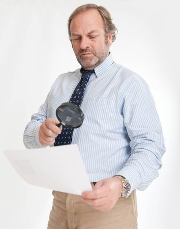Man inspecting a document through a magnifying glass   Stock Photo - 13253518