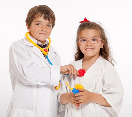 boys toys:  Young boy and girl with medical uniforms and toy doctor instruments