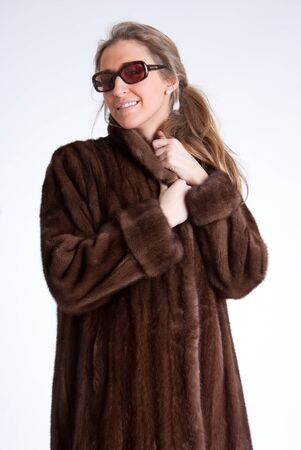 Young woman wearing a mink coat and sunglasses
