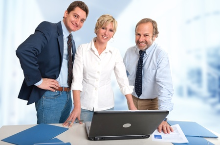 Three business people at the office with happy expressions