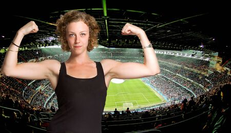 real madrid: Young woman boasting of biceps in a football stadium Stock Photo