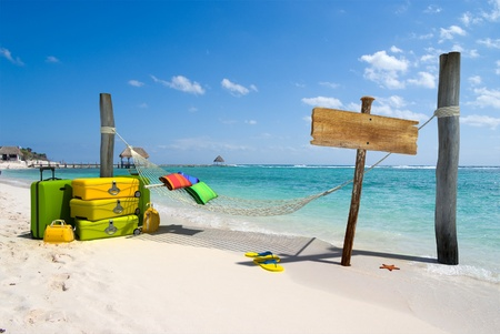 luggage: A hanging hammock, a wooden sign post , a pile of luggage, thongs and starfish on a beach resort
