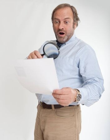 Man with a shocked expression analyzing a document through a magnifying glass Stock Photo - 13253534