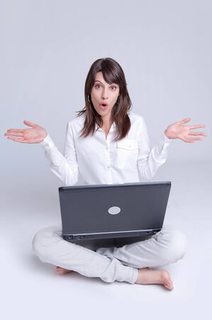 woman searching:   Barefoot young woman using her computer cross-legged on the floor with her arms stretched out with a surprised expression