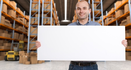 inserting: A man holding a blank board in a distribution warehouse, ideal for inserting your own message
