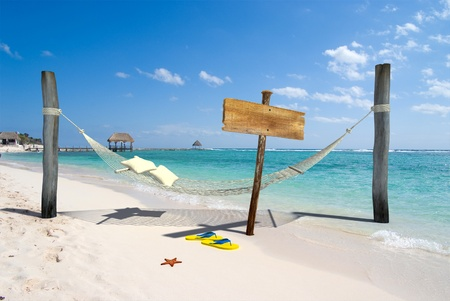 A hanging hammock, a wooden sign post , thongs and starfish on a beach resort photo