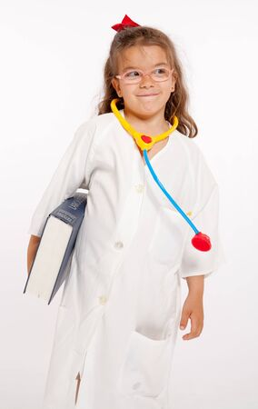 Young girl with a doctors uniform and toy instruments  photo