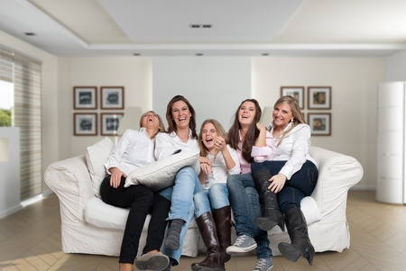 show home: A group of five happy women of different ages laughing in the living room