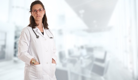 Woman with lab coat and stethoscope  in a business environment Stock Photo - 13354328
