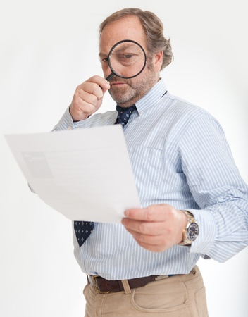 Man inspecting a document through a magnifying glass   photo
