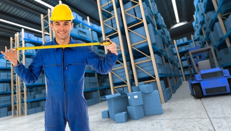 Man with helmet and blue overalls in a distribution warehouse extending a tape measure in blue shades photo
