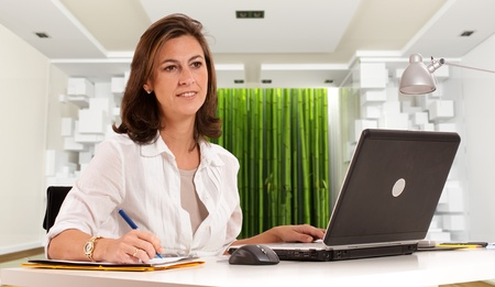 zen interior: Woman sitting at her desk on an cool office environment