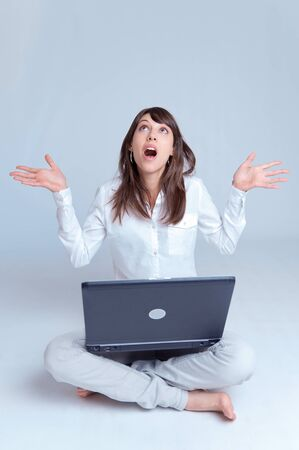 exclaim:   Barefoot young woman using her computer cross-legged on the floor with her arms stretched out with a surprised expression