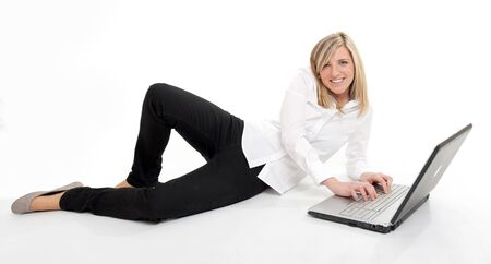 Attractive young blonde using a laptop on the floor Stock Photo - 13441501