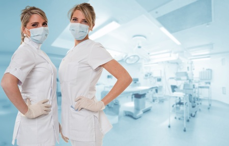 Two attractive healthcare professionals posing in an operating room Stock Photo - 13441719