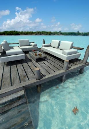 Divani, tavolo basso con rinfresco su un molo dal Mar dei Caraibi Archivio Fotografico