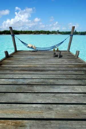 caribbean: Hammock swinging in a pier by a tropical landscape, with a side table laden with fruits and refreshments Stock Photo