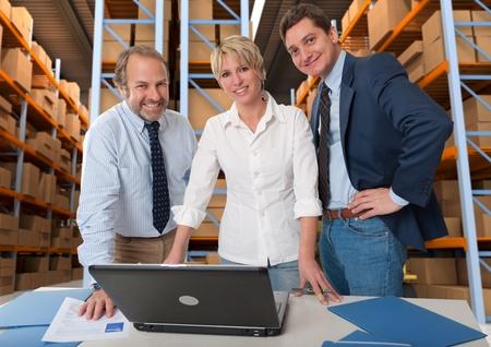 Équipe d'affaires avec un entrepôt de stockage à l'arrière-plan Banque d'images