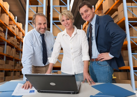 warehouse equipment: Business team with a storage warehouse at the background Stock Photo