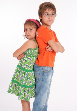 brother sister fight: A boy  and little girl back to back with annoyed expressions